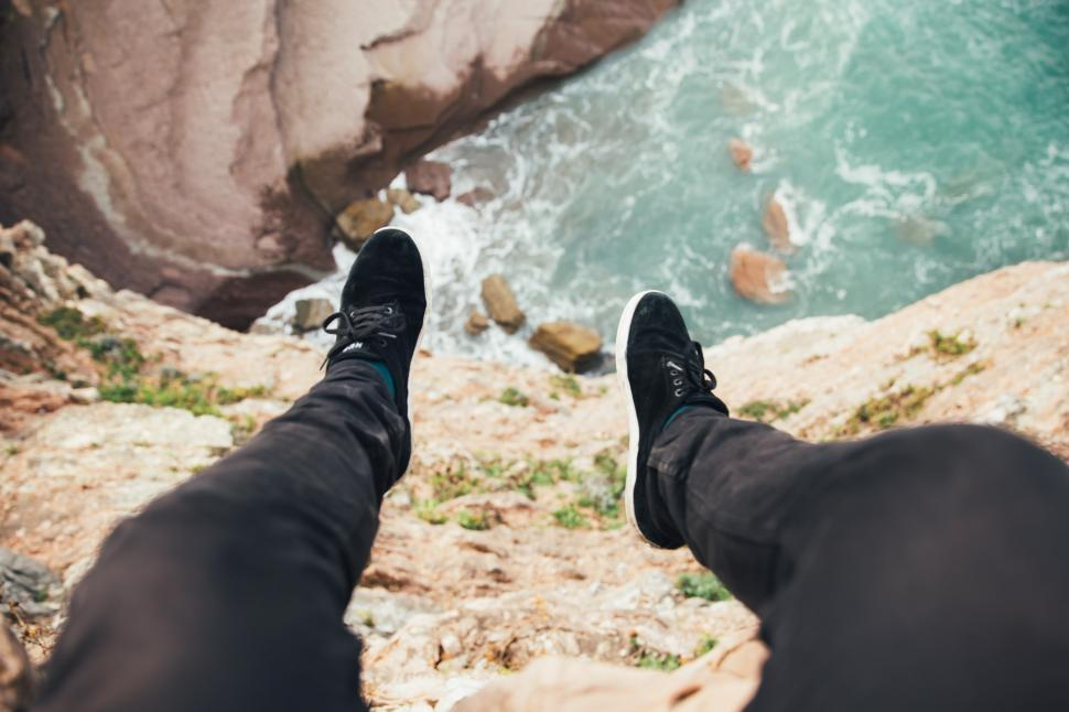Download Free Stock HD Photo of Feet hanging over the edge of a layered rock Online