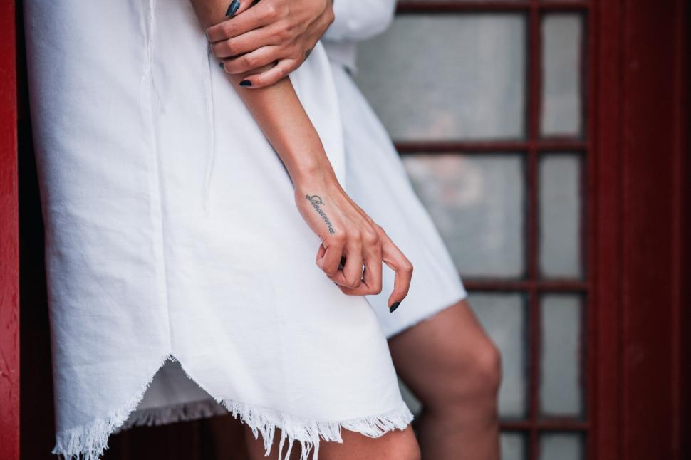 Download Free Stock Photo of A young Caucasian woman in white dress with a tattoo on her hand