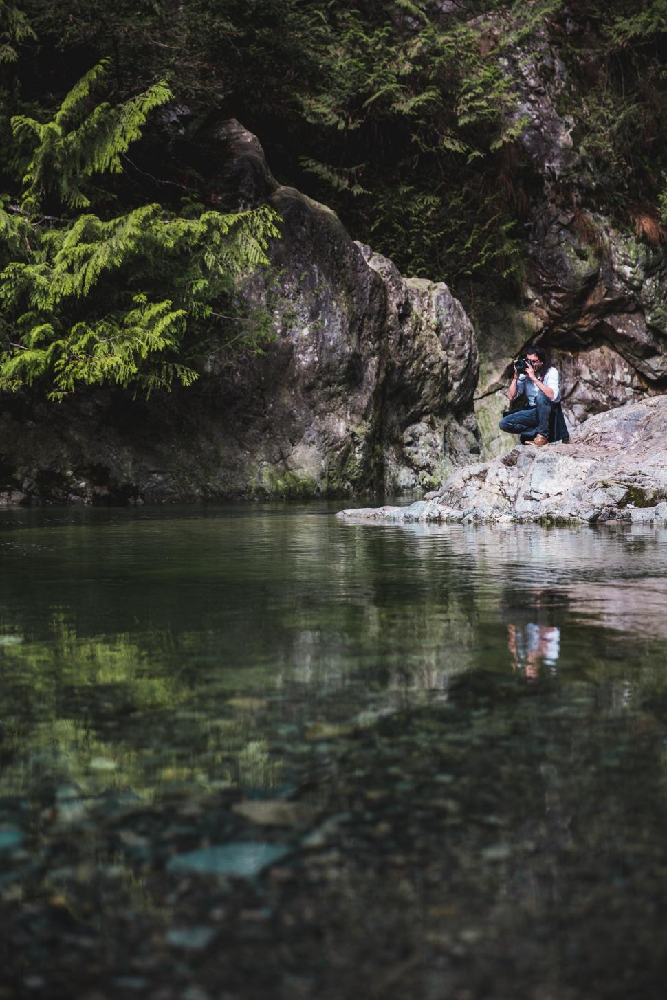 Download Free Stock HD Photo of A nature photographer near a clear water stream Online