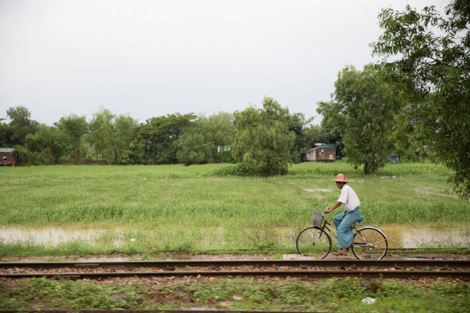 Download Free Stock Photo of A man riding a bicycle near train tracks