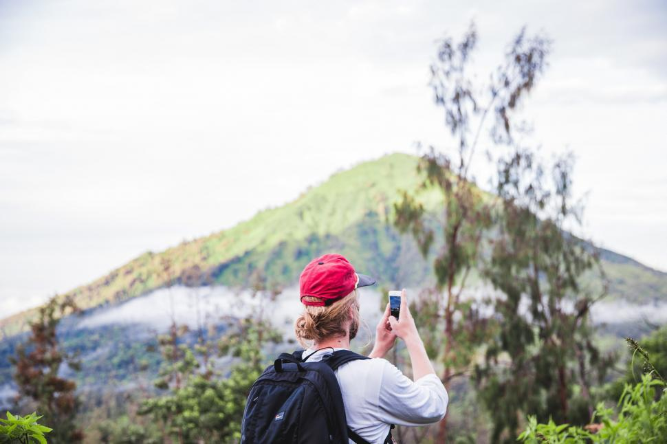 Download Free Stock HD Photo of A hiker clicking picture from his mobile phone Online