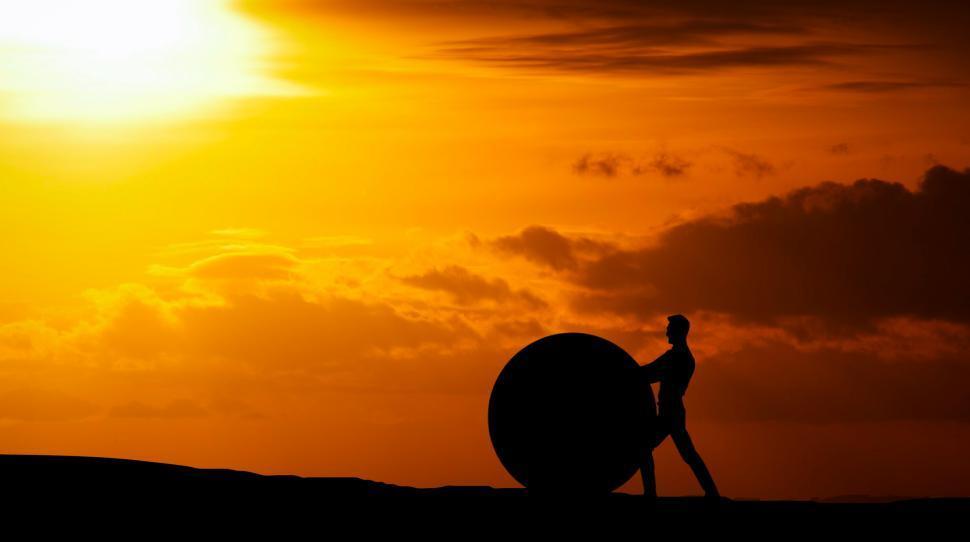 Download Free Stock Photo of man pushing rock ball