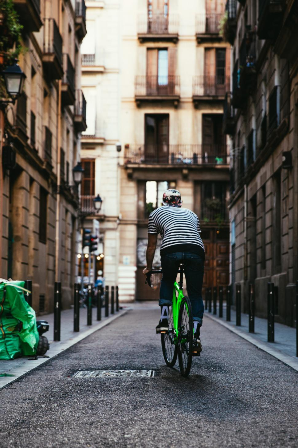 Download Free Stock Photo of Rear view of a biker riding a green bicycle