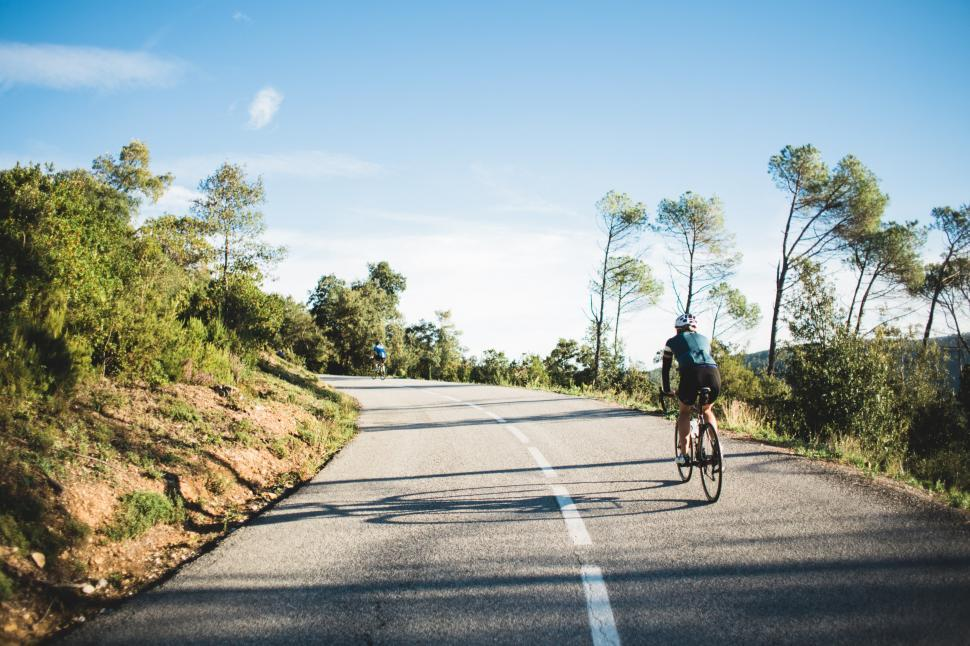 Download Free Stock HD Photo of Country road cyclist on a curvy road Online