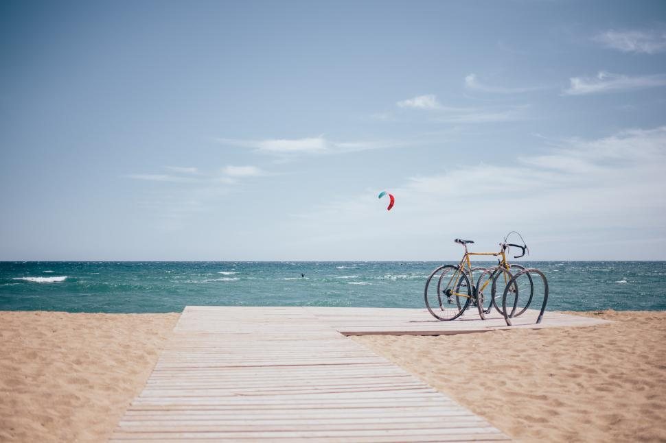 Download Free Stock Photo of Bicycle parked on a boardwalk on an active beach