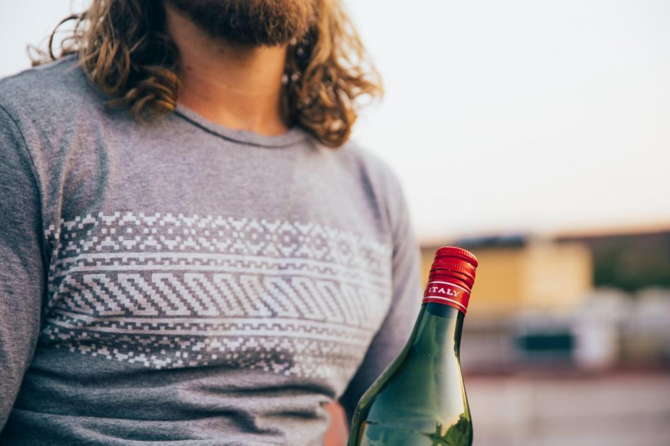 Download Free Stock HD Photo of A bearded caucasian man holding an Italian bottle Online