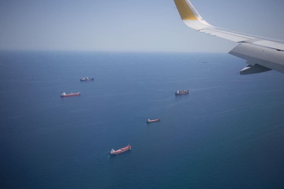 Download Free Stock Photo of Aerial view of ships in the ocean from the airplane window