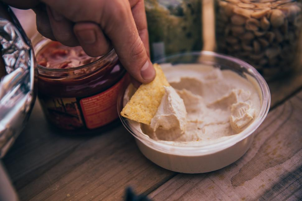 Download Free Stock HD Photo of Dipping Tortilla chip in Hummus Online