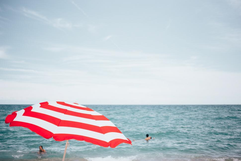 Download Free Stock Photo of A beach umbrella and people swimming