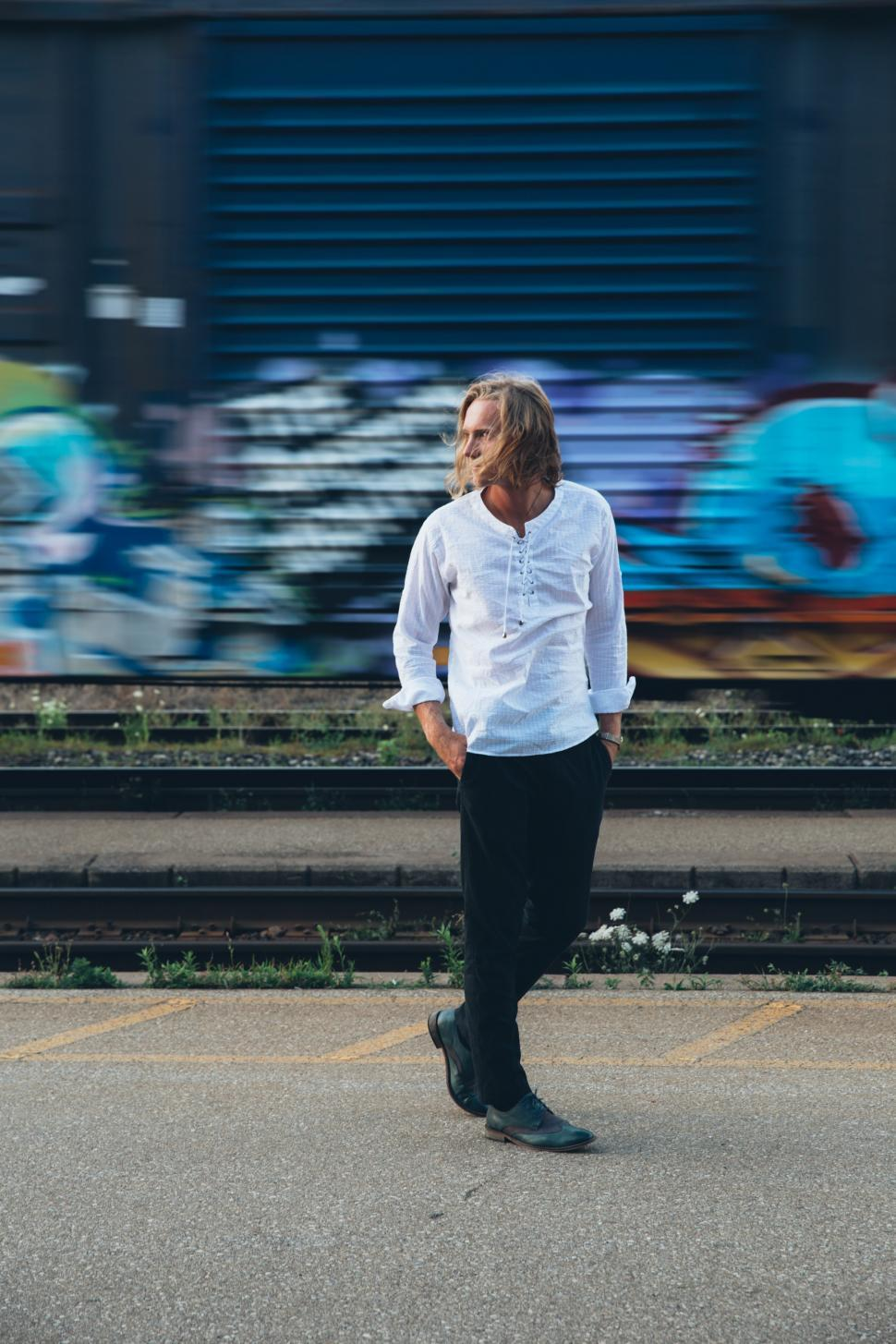 Download Free Stock HD Photo of A fashionable man walks by train tracks Online