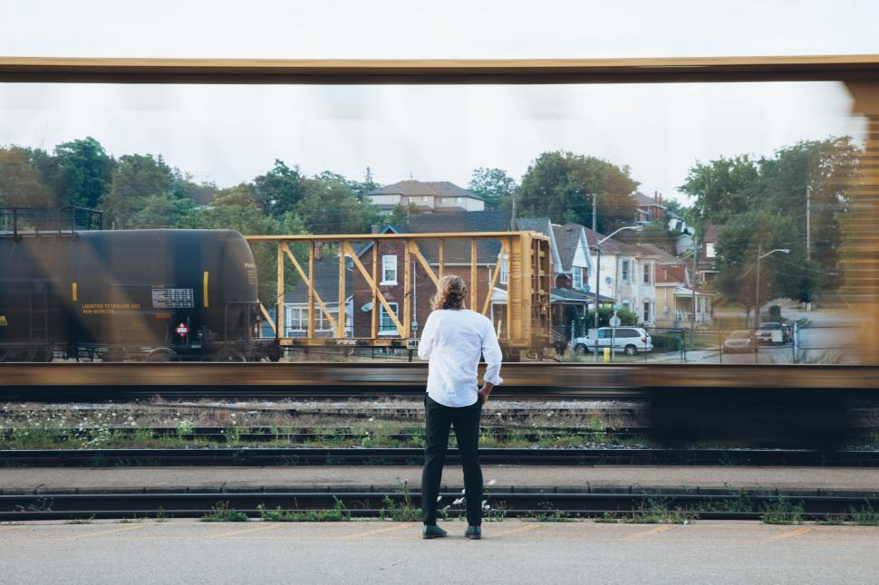 Download Free Stock Photo of A young caucasian man standing near passing train