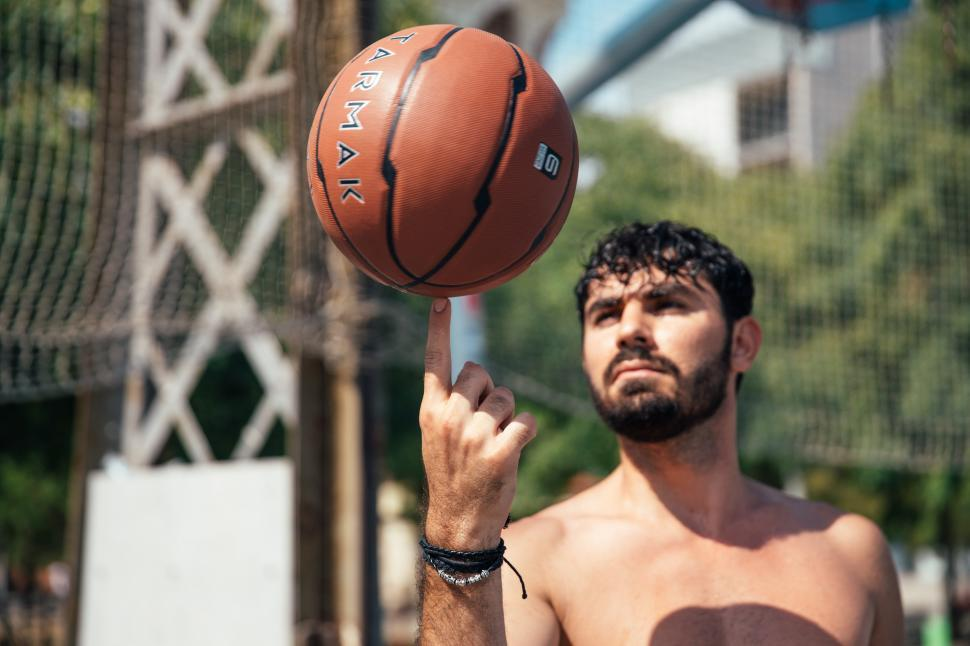 Download Free Stock Photo of A young man spinning basketball on his finger
