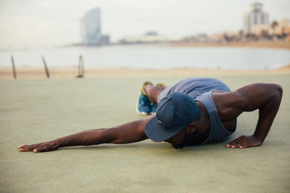 Download Free Stock Photo of A young African man stretching outdoors