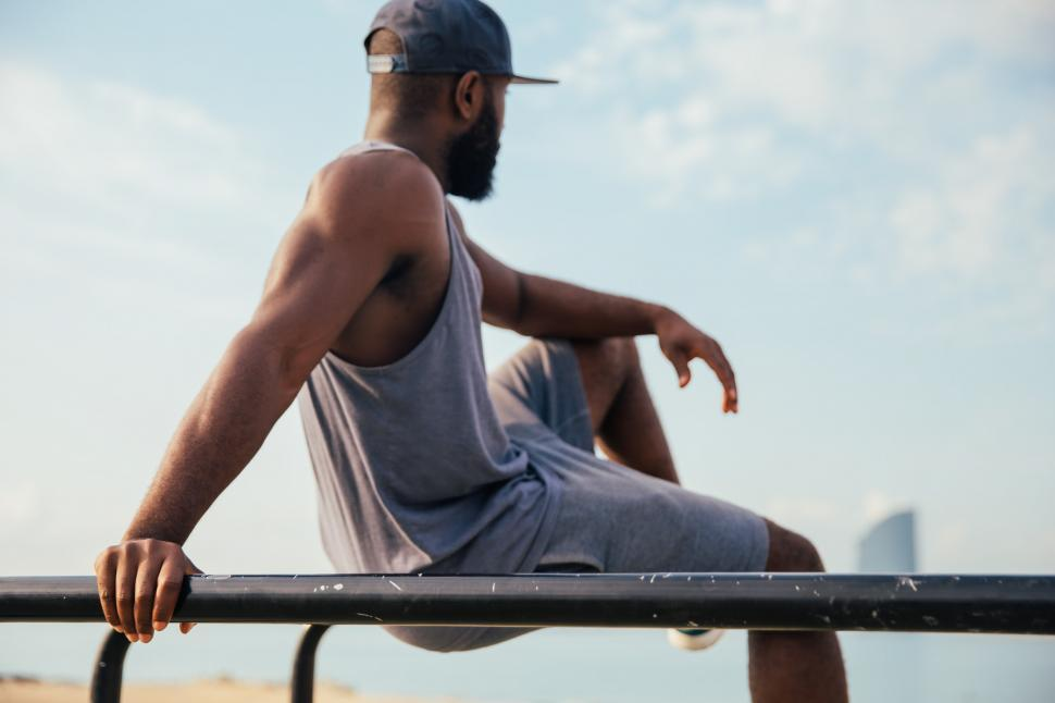 Download Free Stock Photo of A young African man relaxing on workout bars