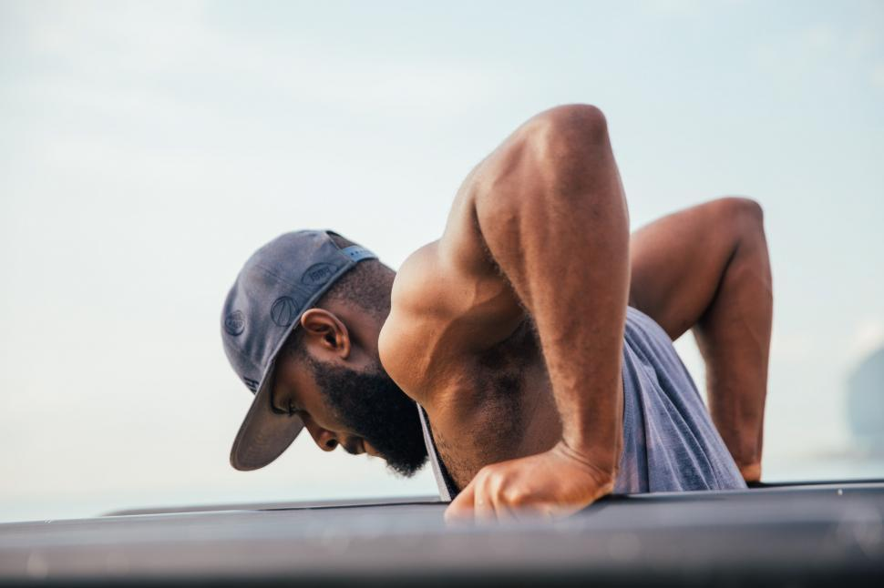 Download Free Stock Photo of A bearded young African man exercising on workout bars
