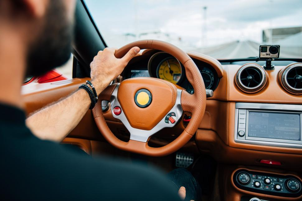 Download Free Stock HD Photo of A car s interior with a bearded young man on driver s seat Online