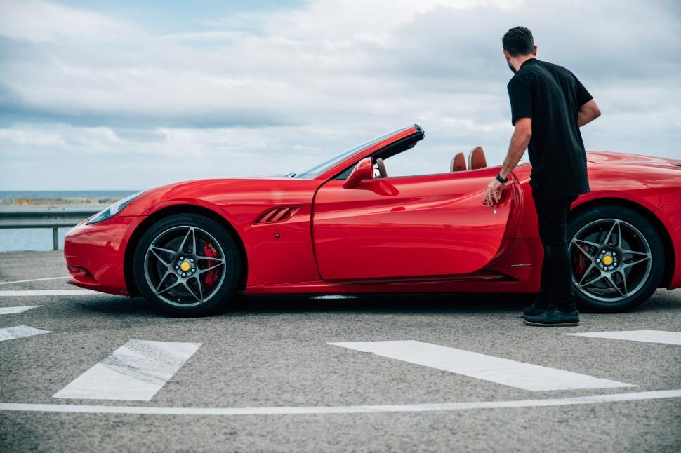 Download Free Stock Photo of A young man getting into a red convertible sports car