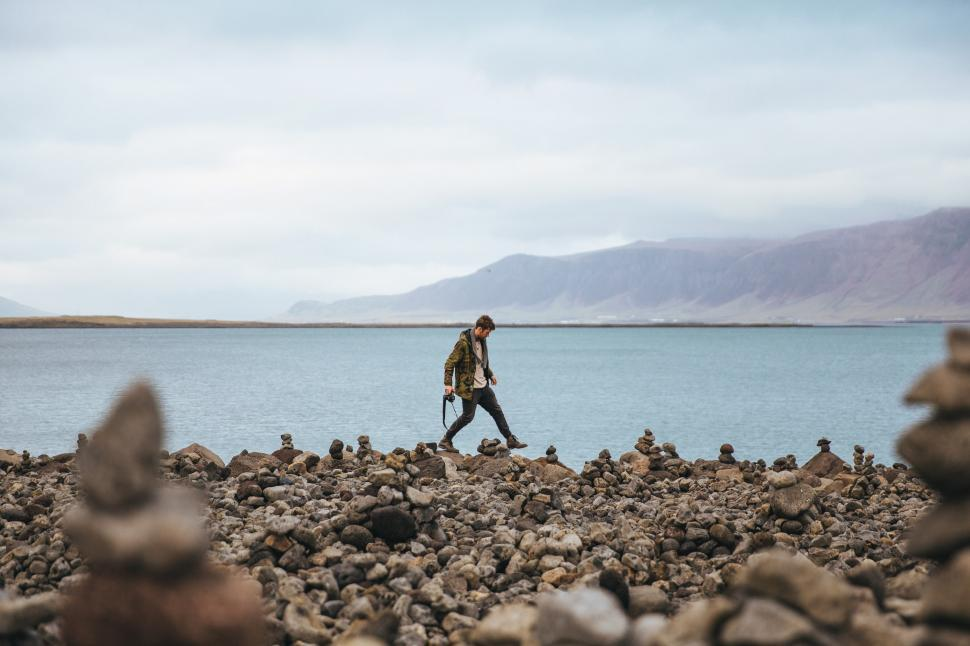 Download Free Stock HD Photo of A young hiker on a stoney shore Online