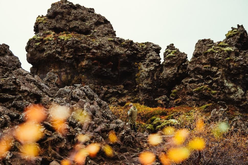 Download Free Stock HD Photo of A photographer at volcanic rocky hills Online