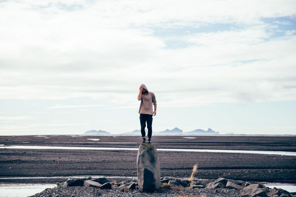Download Free Stock HD Photo of A young Caucasian man standing on a tall rock Online