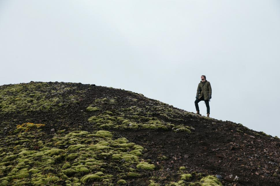 Download Free Stock HD Photo of A hiker in standing on a moss-grown rocky hill Online