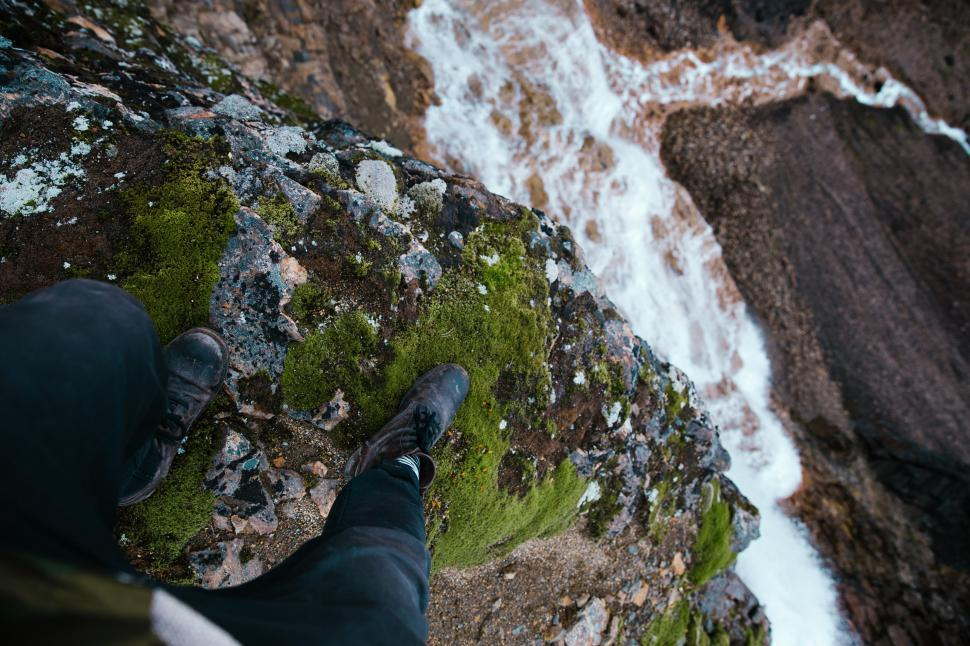 Download Free Stock HD Photo of Feet dangling over moss grown rock edge Online