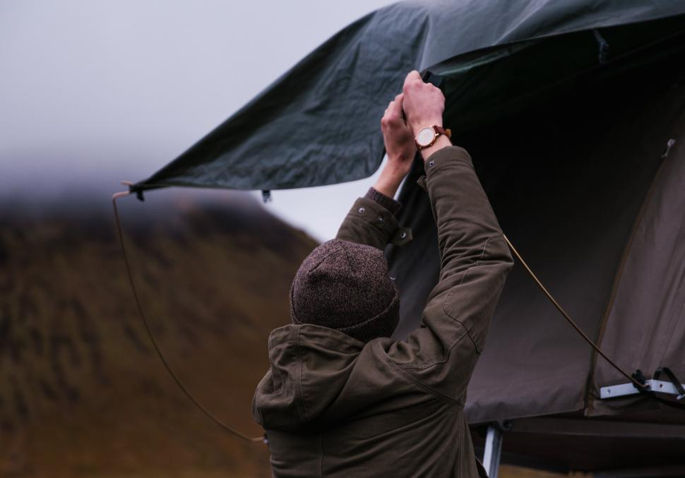 Download Free Stock Photo of A young caucasian man setting up tent