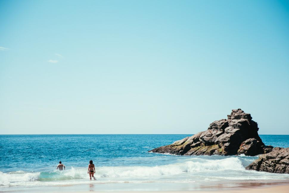 Download Free Stock HD Photo of A young Caucasian man and a woman swimming in the ocean Online
