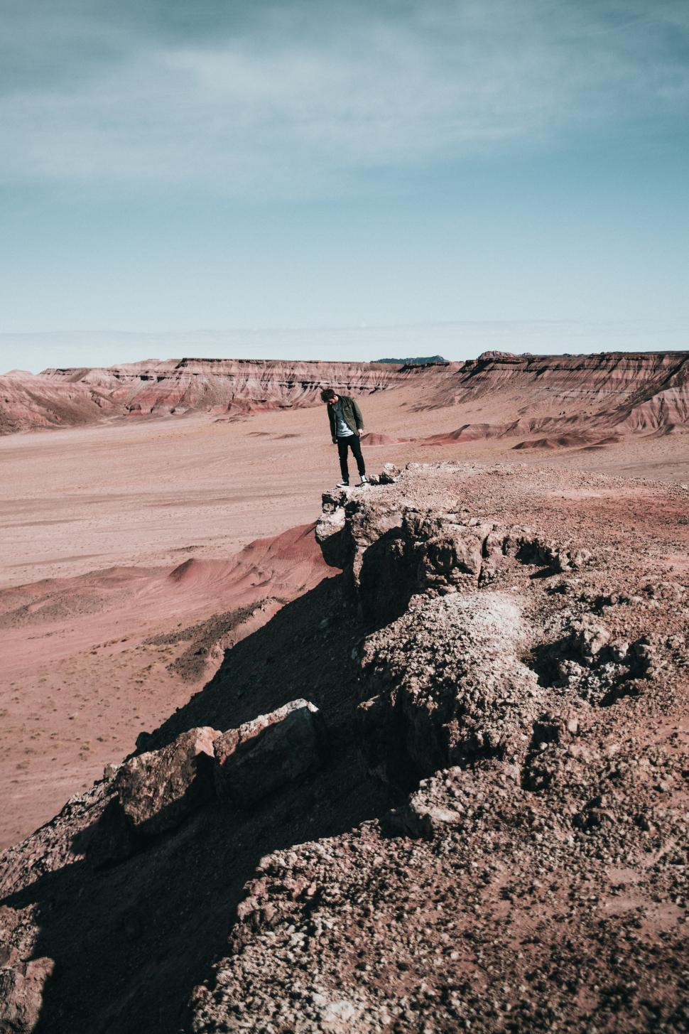 Download Free Stock HD Photo of A hiker peaks over a rocky edge Online