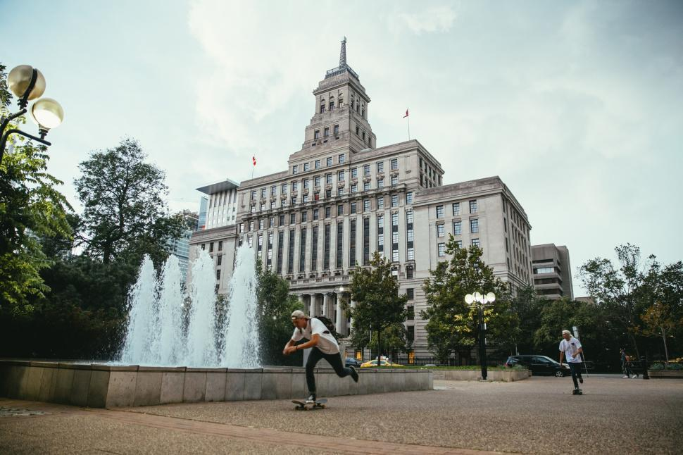 Download Free Stock HD Photo of Young Caucasian skateboarders ride past a fountain Online