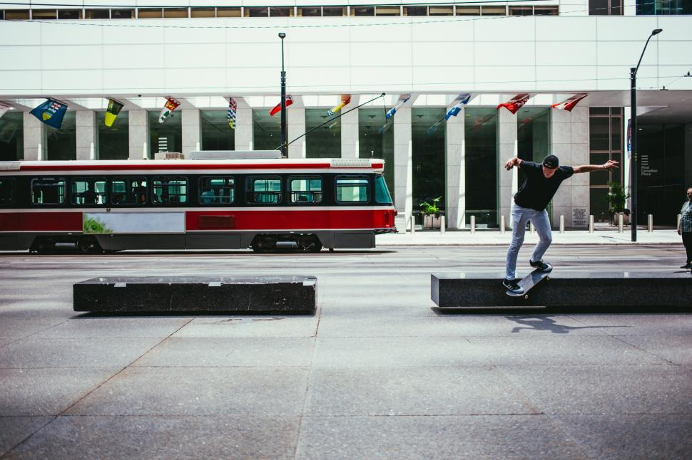 Download Free Stock HD Photo of A young Caucasian skateboarder in action near a city building Online