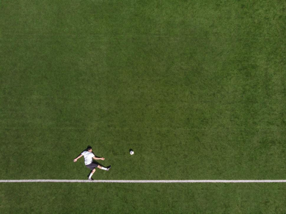 Download Free Stock Photo of Aerial view of a striker kicking the football