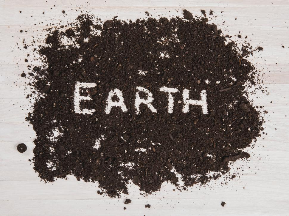 Download Free Stock Photo of The text  EARTH  written out in dark soil on a white wooden surface