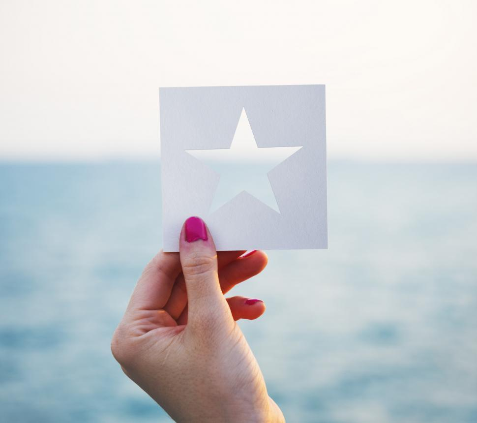 Download Free Stock Photo of A female hand holding a star shaped paper cut out template