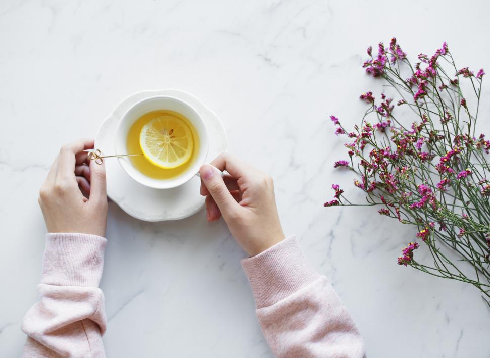 Download Free Stock Photo of Flat lay of hands holding a lemon tea cup and on saucer