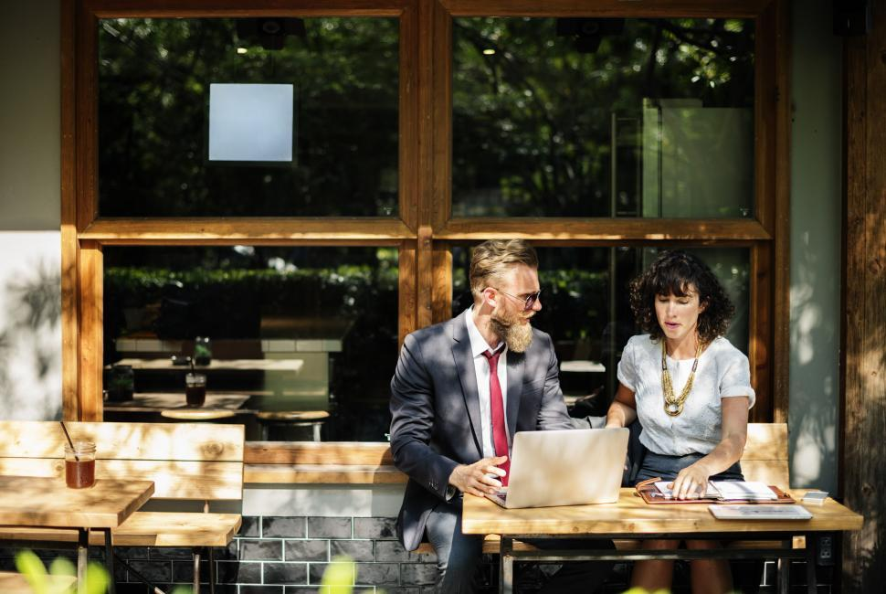 Download Free Stock HD Photo of Portrait of two business people discussing at an outdoor restaur Online