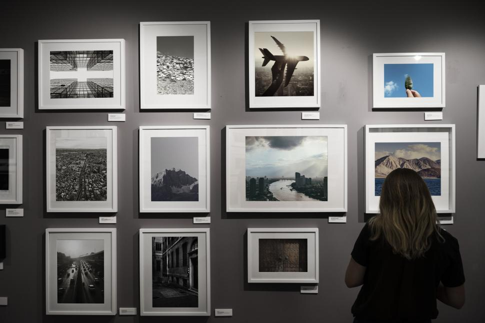 Download Free Stock Photo of Rear view of a woman looking at framed photograph on an exhibiti