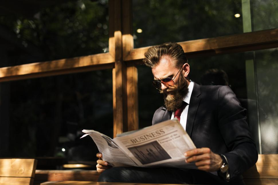 Download Free Stock HD Photo of A bearded man wearing sunglasses reading a newspaper Online