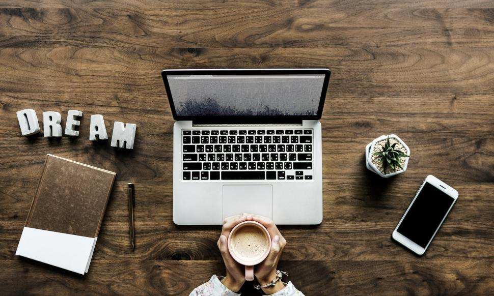Download Free Stock Photo of Flat lay of a laptop and hands holding a coffee mug
