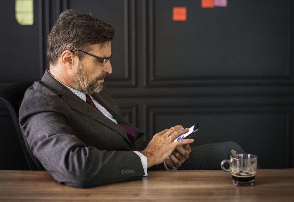 Download Free Stock Photo of A bearded businessman looking at his mobile phone