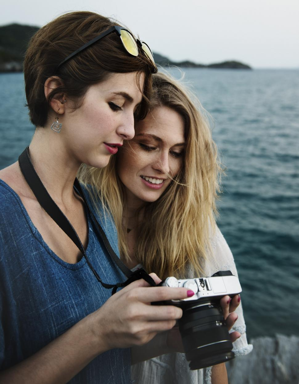 Download Free Stock Photo of Two young women looking at their photograph on the cam