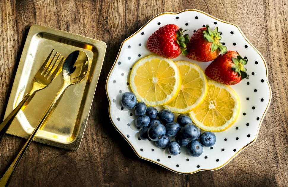 Download Free Stock Photo of Flat lay of strawberries, lemon slices and black grapes
