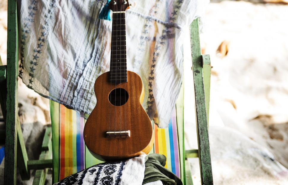 Download Free Stock HD Photo of Close up of a guitar on a beach chair Online
