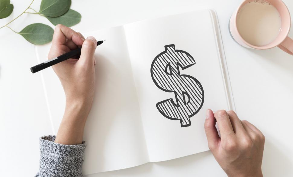Download Free Stock HD Photo of Over the head view of a dollar sign drawn on white notebook Online