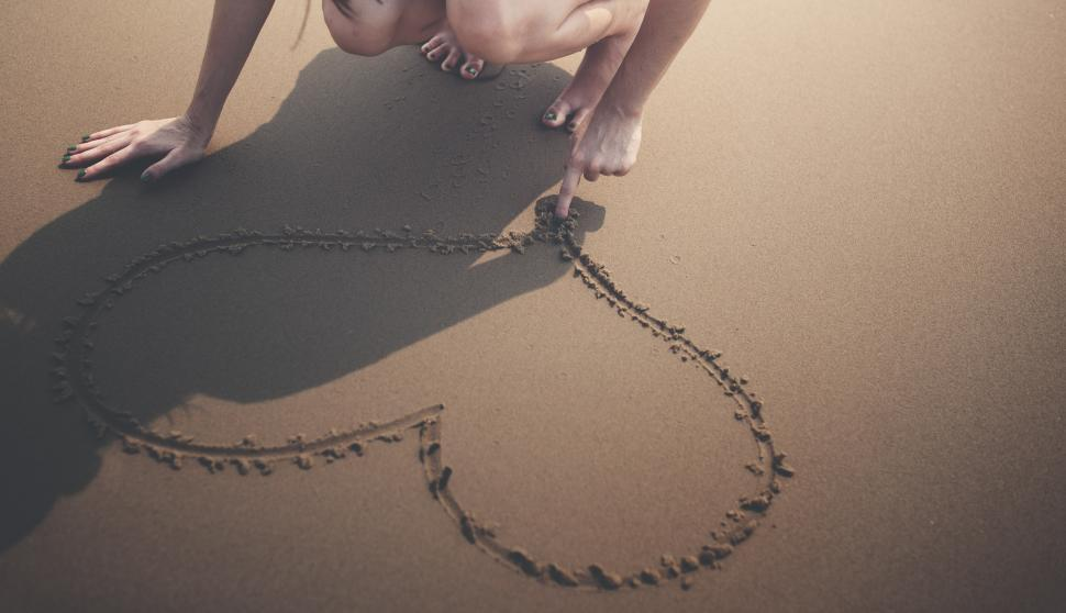 Download Free Stock HD Photo of A young woman s hand drawing a heart in the sand Online