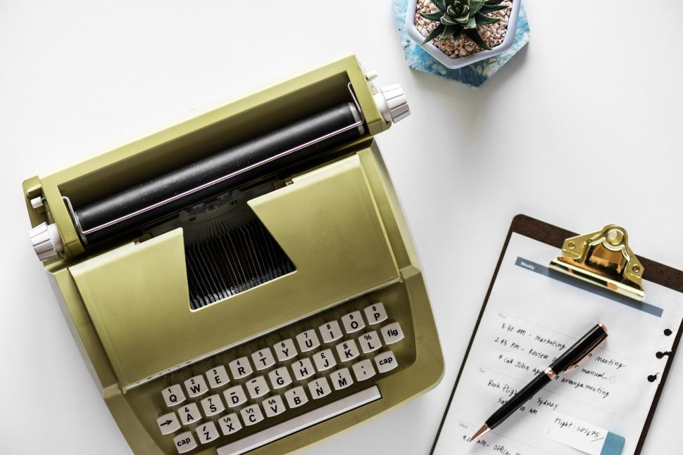 Download Free Stock HD Photo of Vintage typewriter alongside a clipboard Online