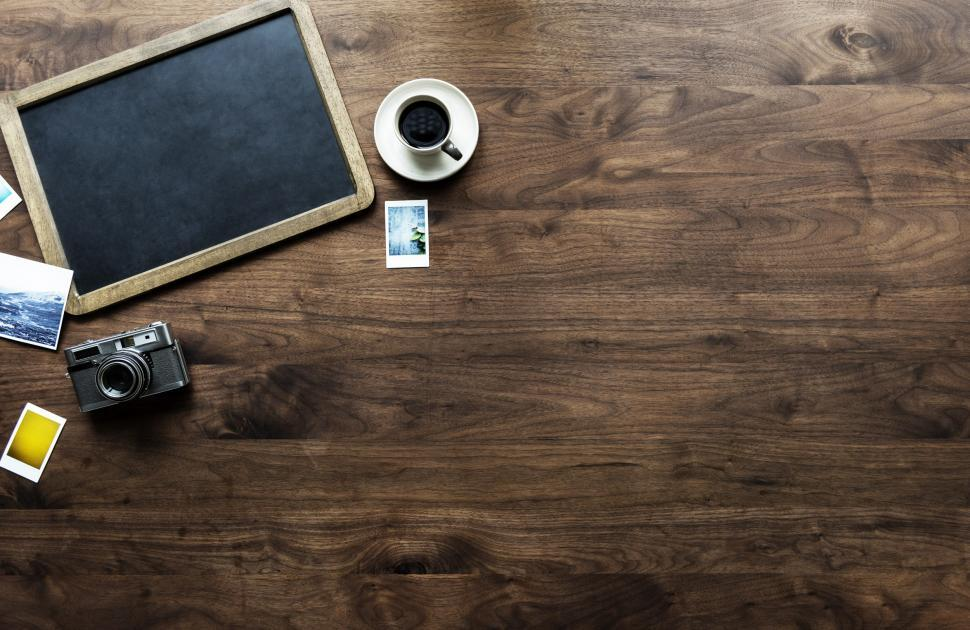 Download Free Stock Photo of Flat lay of a slate blackboard and vintage camera on hardwood su