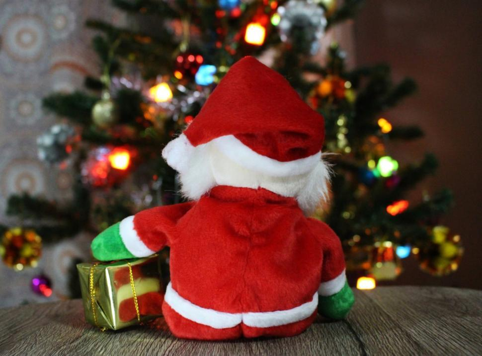 Download Free Stock HD Photo of Santa with present looks at Christmas Tree  Online