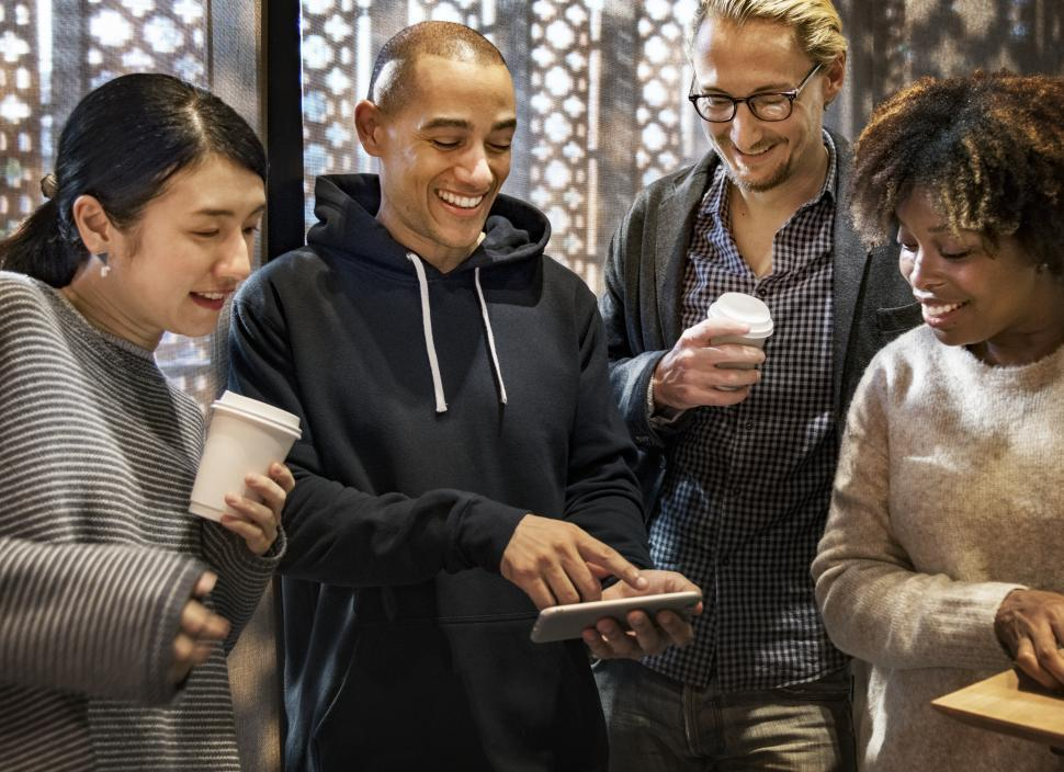 Download Free Stock Photo of Multiethnicity people having fun while looking at their colleague s mobile phone screen