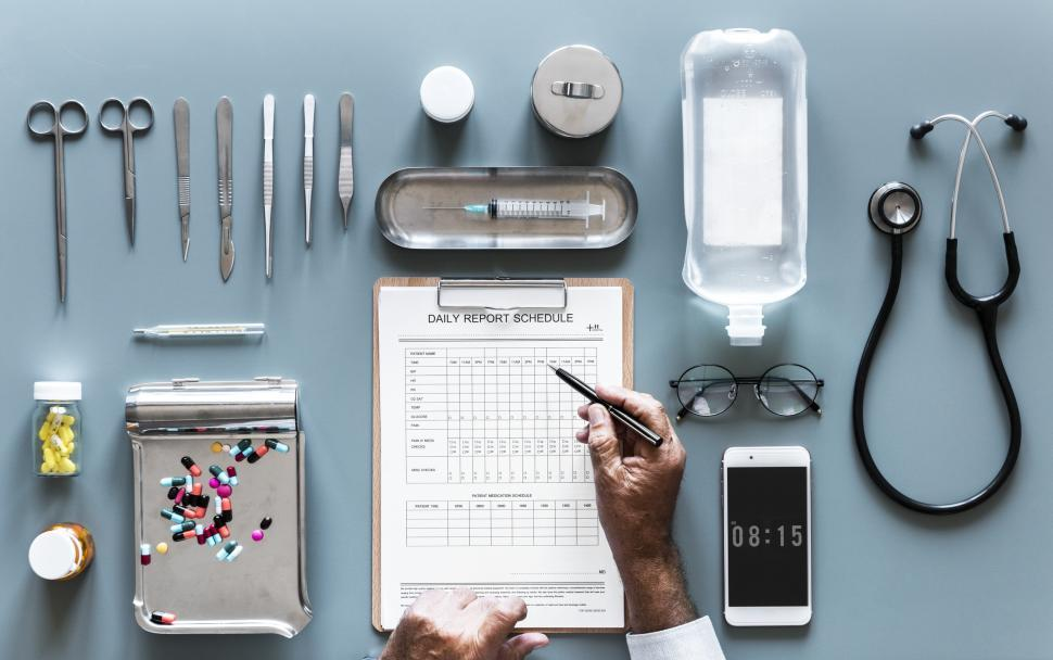 Download Free Stock Photo of Flat lay of doctor s hands checking daily report schedule surrounded with medicines and medical instruments